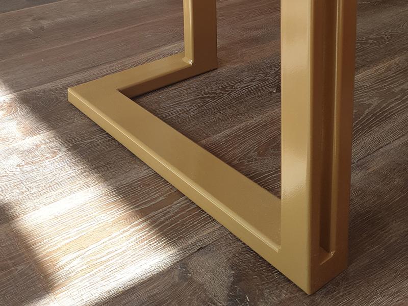 Détail des pieds du présentoir en métal doré