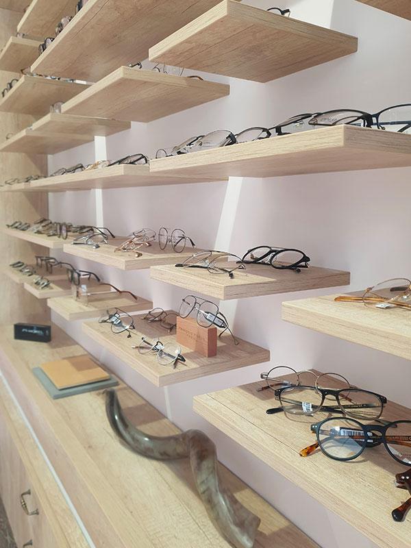 Présentoirs et meubles de rangement aspect bois dans une boutique d'optique