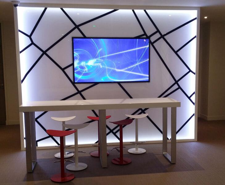 Table haute et tabourets pour espace d'échanges avec support pour télévision