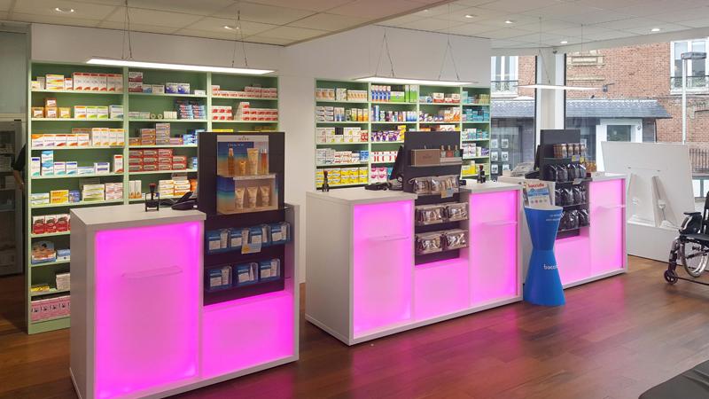 Aménagement pharmacie Le Havre avec des comptoirs roses rétroéclairés