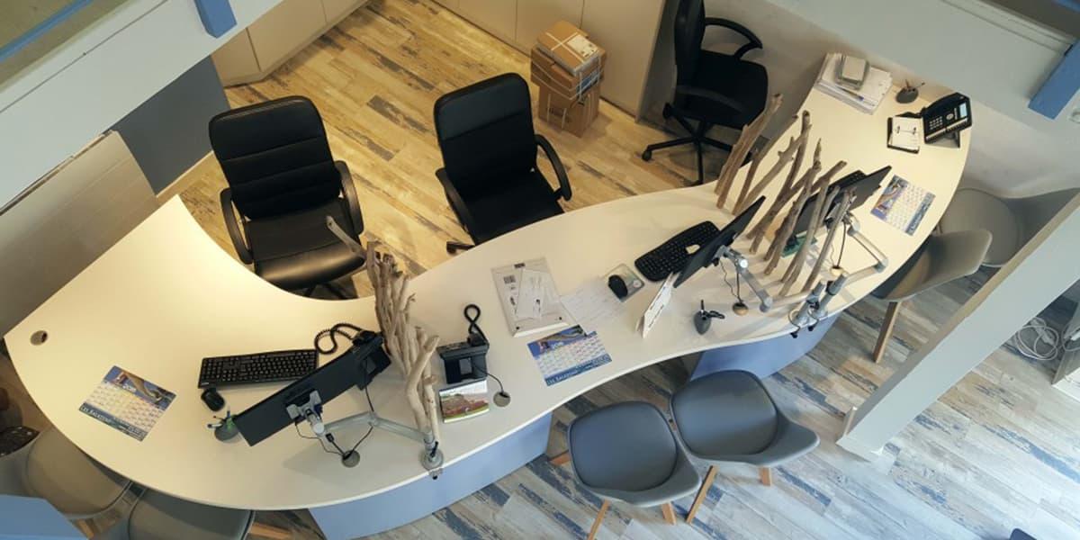 Vue de dessus d'un bureau aux courbes optimisées pour la création de trois espaces d'accueil au sein d'une agence de voyages